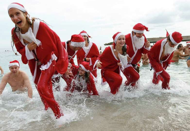 People dressed up as Santa Claus enjoy a traditional Christmas bath on December 23, 2012 in Monaco.