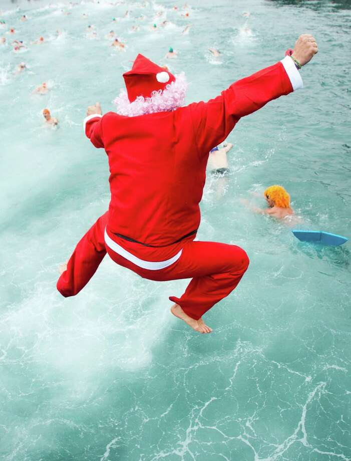 A competitor dressed up as Santa Claus jumps into the sea during the 103rd Barcelona Traditional Christmas Swimming Cup at the Old Harbour of Barcelona on December 25, 2012 in Barcelona, Spain. The Copa Nadal is organised by the Barcelona Swimming Club and involves competitors swimming across some 200 metres of water in the harbour. Launched in 1908 the event has only been suspended three times when the Spanish Civil War interrupted proceedings between 1936 and 1938. Photo: David Ramos, Getty Images / 2012 Getty Images