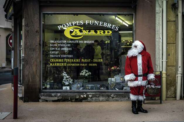 A man dressed as Santa Claus stands in front of a funeral home on December 24, 2012 in Gueugnon. Photo: JEFF PACHOUD, AFP/Getty Images / AFP ImageForum