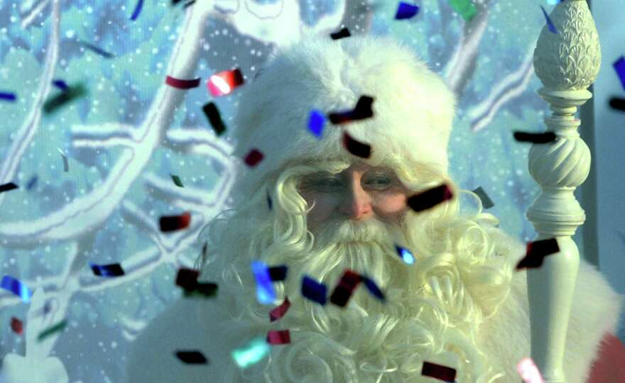 An actor dressed as Ded Moroz (Grandfather Frost), the Russian Santa Claus, smiles through smoke fro