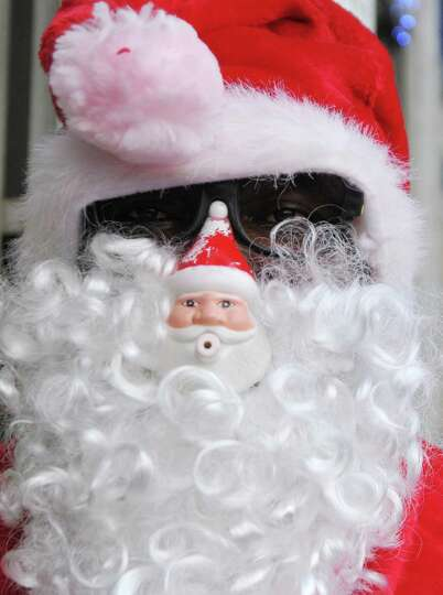 A man dressed as Santa Claus poses for a picture as he stands in front of a toy store in Abidjan, on
