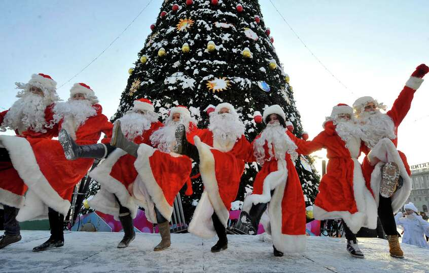 People wearing Father Frost outfits dance during a traditional pre-New Year parade in central Minsk