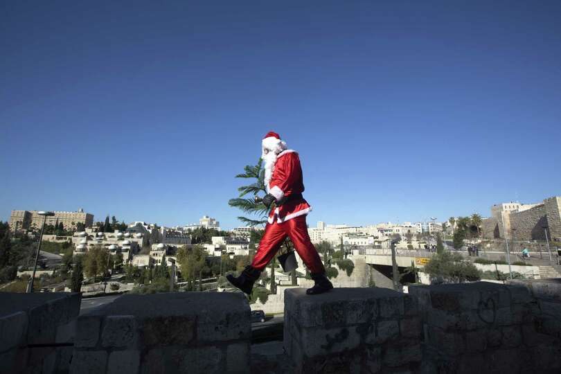 A Palestinian man dressed up as Santa Claus carries a Christmas tree and rings a bell as he walks al