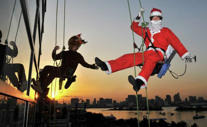 Workers in a Santa Claus (R) and reindeer (L) costumes clean windowpanes outside a 31-metre-high bui