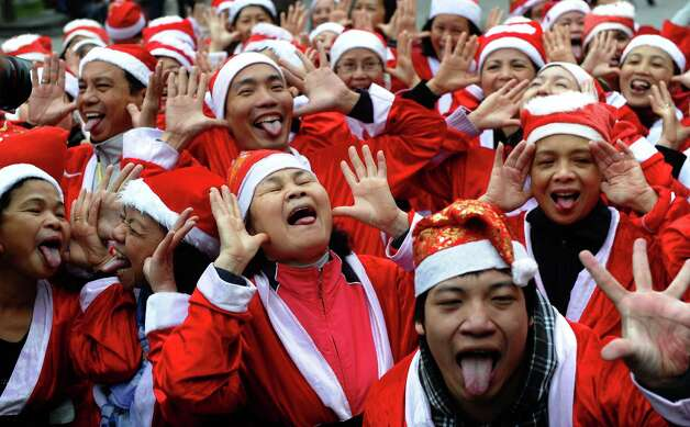 Members of a local Smiling Yoga club wearing Santa Claus costumes perform at a public park in Hanoi on December 23, 2012. Churches, shops, restaurants and shopping mails are decorated in the Southeast Asian nation with some six million catholics preparing to celebrate Christmas. Photo: HOANG DINH NAM, AFP/Getty Images / AFP