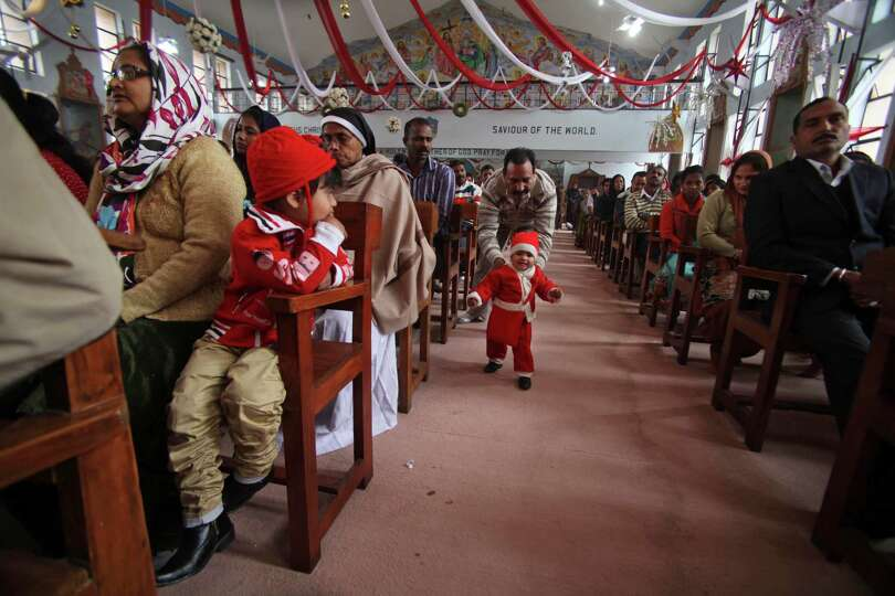 A child dressed in Santa Claus clothes walks during Christmas prayers at the Saint Mary's Garrison C
