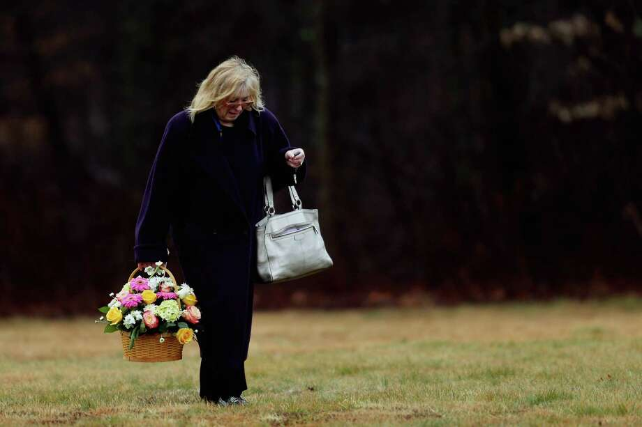 MONROE, CT - DECEMBER 17:  A woman carries a basket of flowers at the funeral services for six year-old Noah Pozner, who was  killed in the shooting massacre in Newtown, CT, at B'nai Israel Cemetery on December 17, 2012 in Monroe, Connecticut. Today is the first day of funerals for some of the twenty children and seven adults who were killed by 20-year-old Adam Lanza on December 14, 2012.  (Photo by Spencer Platt/Getty Images) Photo: Spencer Platt / Getty Images