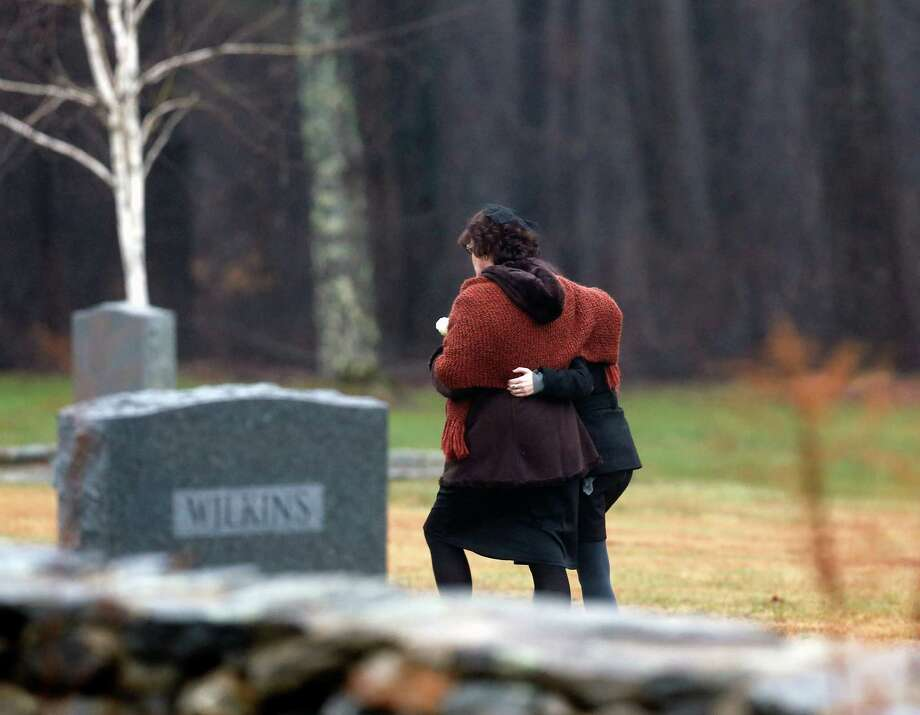 Veronique Pozner, left, embraces a young girl as she arrives at B'nai Israel Cemetery for burial services for her 6-year-old son Noah Pozner, Monday, Dec. 17, 2012, in Monroe, Conn. Noah Pozner was killed when Adam Lanza walked into Sandy Hook Elementary School in Newtown, Conn., Friday and opened fire, killing 26 people, including 20 children, before killing himself. (AP Photo/Julio Cortez) Photo: Julio Cortez / Associated Press