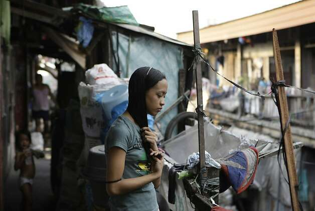 Jessa Balote, shown outside her shantytown home, used to help her family collect garbage at a dump. Photo: Aaron Favila, Associated Press