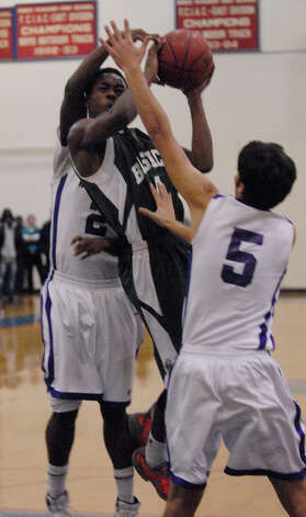 Bassick's Kobe Ancrum fights to get the ball above Westhill's Terrell Middleton, left, and Evan Skoparantzas Bassick and Westhill High Schools face off in the Paul Kuczo Holiday BasketballTournament at Brien McMahon High School in Norwalk, Conn., Dec. 26, 2012. Photo: Keelin Daly / Stamford Advocate Riverbend Stamford, CT