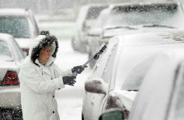 Helen Earley cleans off her car in the parking lot of Hawkins Market in Ashland, Ohio Wednesday, Dec. 26, 2012 after buying groceries. (AP Photo/Ashland Times-Gazette, Tom E. Puskar) Photo: Tom E. Puskar