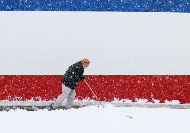 Dan Switzer, owner of the Dairy Queen on Bechtle Avenue, shovels snow although the store was closed due to the weather on Wednesday, Dec. 26, 2012, in Springfield, Ohio. (AP Photo/The Springfield News-Sun, Barbara J. Perenic) Photo: Barbara J. Perenic