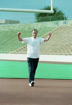 President George H.W. Bush flexes his arms for photographers as he went for a jog at Alamo Stadium in San Antonio, Oct. 8, 1992. The President had been in San Antonio to sign the North America Free Trade Agreement. Photo: Marcy Nighswander, Associated Press File Photo / 1992 AP