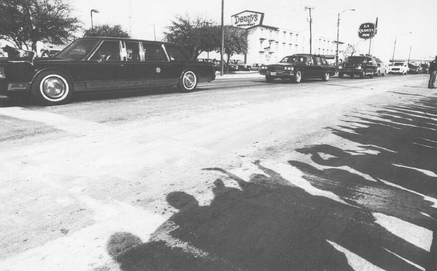 A crowd watches as a limo carrying President George H.W. Bush drives through San Antonio Feb. 26, 19