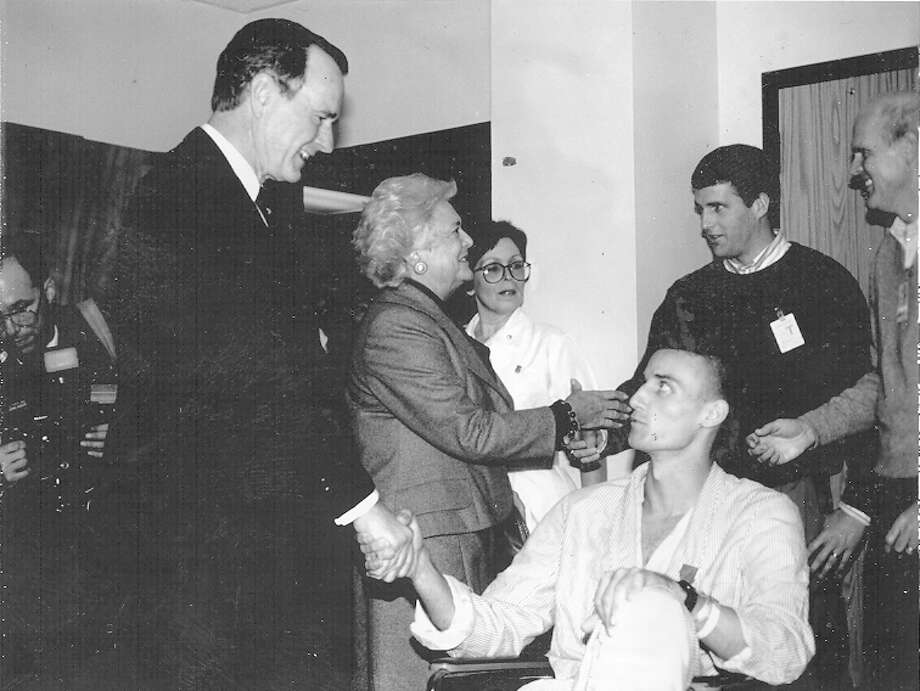 Army Sgt. Kyle Kelley looks up at President George H.W. Bush during Bush's visit to soldiers wounded in Panama recovering at Wilford Hall Medical Center on Dec. 31, 1989. Kelley, 20, received fragment wounds in his lower back on Dec. 20. He is from Santee, Calif., and has served in the Army nearly three years. Photo: San Antonio Light File Photo