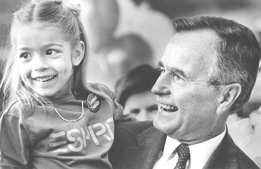 Vice President George H.W. Bush holds Julie Taylor after picking her out of the crowd during his vis