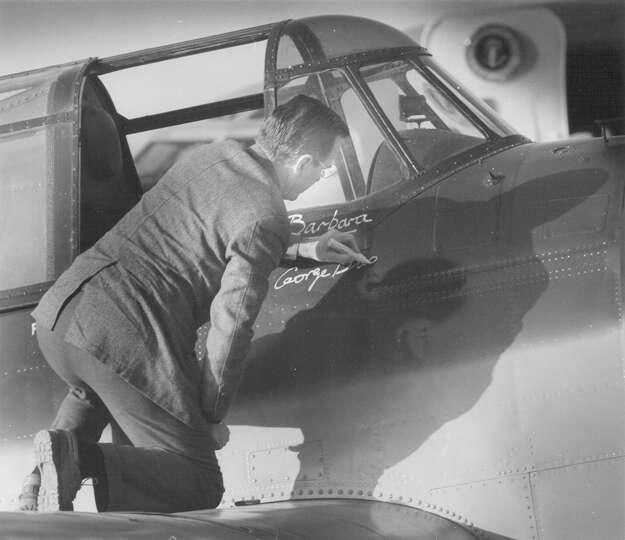 President-elect George H.W. Bush signs his name below wife Barbara's on a World War II-era bomber pl