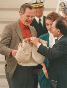 President-elect George H.W. Bush accepts a quail bag for his hunting expedition from Bee County Chamber of Commerce President Henry Medina on Dec. 26, 1988. Photo: San Antonio Express-News File Photo