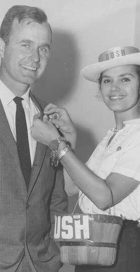 Mrs. Phillip Carrington pins a campaign button on U.S. Senate hopeful George H.W. Bush's lapel on Se