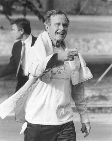 Wearing a T-shirt given to him by the Sunshine Cottage in San Antonio, President George H.W. Bush greets the children of the Sunshine Cottage School for Deaf Children Oct. 8, 1992, after his jog at Alamo Stadium. Photo: San Antonio Express-News File Photo