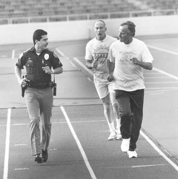 President George H.W. Bush is kept company by San Antonio Police Sgt. Victor Balderas during his rounds on the track at Alamo Stadium Oct. 8, 1992. The president invited Balderas to accompany him. The man in the back is a Secret Service man. Photo: San Antonio Express-News File Photo