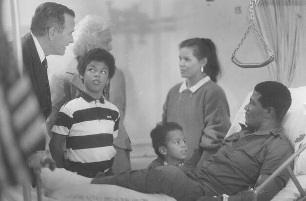 President George H.W. Bush visits with Army Staff Sgt. Lloyd Johnson and his family during a trip to Brooke Army Medical Center on Dec. 31, 1989. Johnson, of Akron, Ohio, had a partial amputation of his left foot as a result of the combat in Panama. His wife Estela, who is Panamanian, speaks to First Lady Barbara Bush. Johnson's sons are Franklin, 10 (left center), and Scott, 5. Photo: San Antonio Express-News File Photo