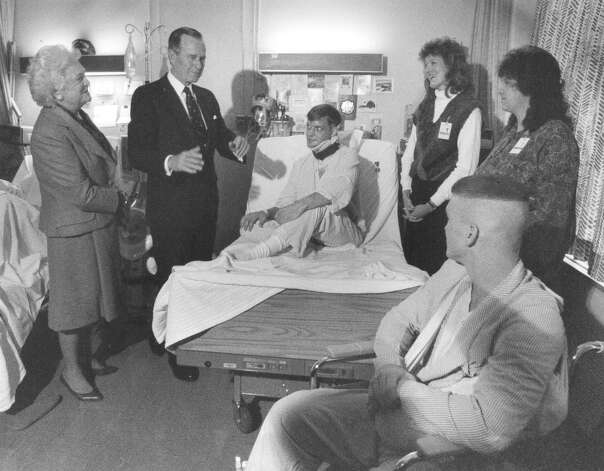 First Lady Barbara Bush and President George H.W. Bush talk with Marine Sgt. Gregory A. Johnson (center) and Army Pfc. Wallace Brooks (foreground right) during a visit to Wilford Hall Medical Center on Dec. 31, 1989. The woman just to the right of Johnson is his fiancée, Laura Smith. The other woman is unidentified. Johnson and Brooks were wounded in Panama on Dec. 20, and among the first to be evacuated to San Antonio. Johnson was wounded in the head and left hand, and Brooks received a shell fragment wound in his left shoulder. Photo: San Antonio Express-News File Photo