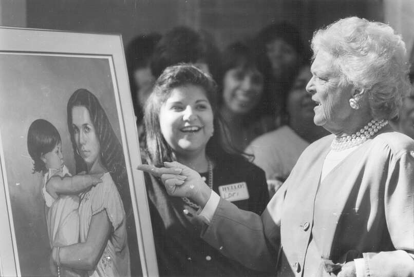 First Lady Barbara Bush admires the painting given to her by Avance Child Development Center on Sept
