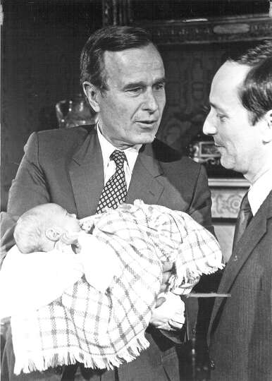 Vice President George H.W. Bush talks to Jeff Wentworth while holding an unidentified baby on Oct. 2