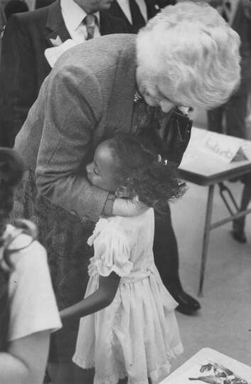 Second Lady Barbara Bush hugs an unidentified girl in November 1981.