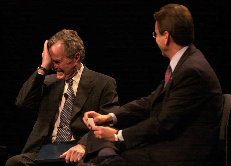 Former President George H.W. Bush laughs after comments made by Coldwell Bankers' President and CEO