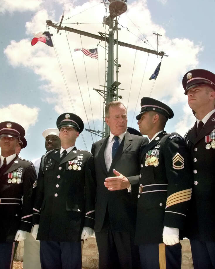 Former President George H.W. Bush talks with Sgt. 1st Class Donald M. Rangel (center right) and Spc. Toby S. Hensley (center left), both members of the Fort Sam Houston color guard, in front of the Nimitz Museum in Fredericksburg, where Bush had just cut the ribbon to open the George Bush Gallery of the museum on June 11, 1999. Photo: Tom Reel, San Antonio Express-News File Photo / SAN ANTONIO EXPRESS-NEWS