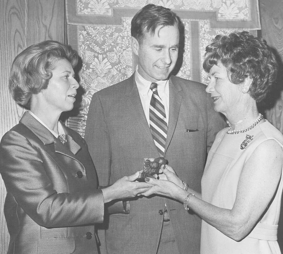 Mrs. James Shand III, National Board of Planned Parenthood of the World Population, presents Mrs. George Luhn a sculpture for her work as U.S. Rep. George H.W. Bush looks on Feb. 7, 1969. Photo: San Antonio Express-News File Photo