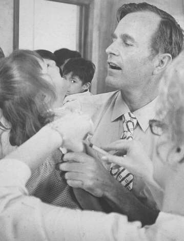 George H.W. Bush aides nurse Mrs. Oscar Gutierrez in administering a shot to Sobada Duquee, 3, daughter of Mrs. Carolina Duquee in this undated file photo. Photo: San Antonio Express-News File Photo