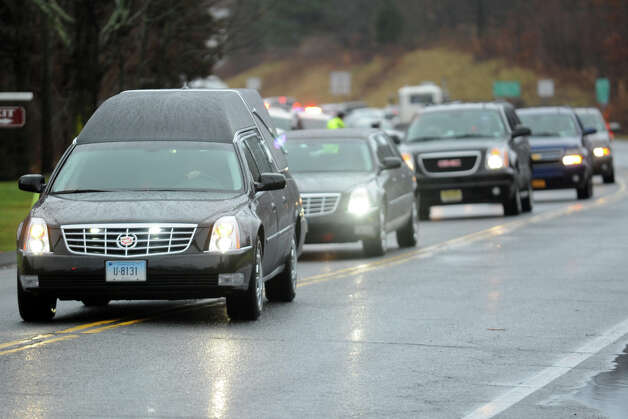 A hearse carrying the remains of Mary Joy Sherlach arrives at St. Stephen Church, in Trumbull, Conn., prior to a funeral mass Dec. 21st, 2012. Sherlach was a school pychologist at Sandy Hook Elementary School, in Newtown, and died in the mass shooting there last Friday. Photo: Ned Gerard / Connecticut Post