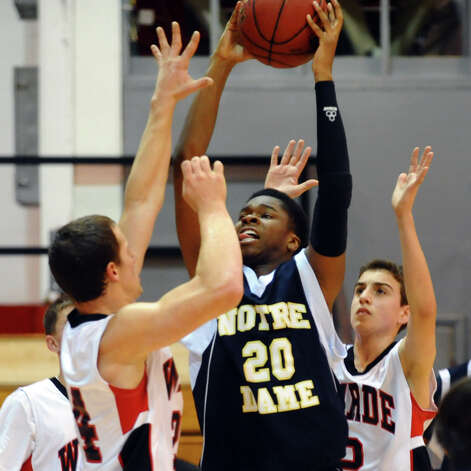 Fairfield Warde's Max Garrett looks to block a shot attempt by Notre Dame of Fairfield's #20 Jaylen Jennings, during semifinal action of the Fairfield Prep Holiday Classic basketball tournament in Alumni Hall at Fairfield University in Fairfield, Conn. on Wednesday December 26, 2012. Photo: Christian Abraham / Connecticut Post