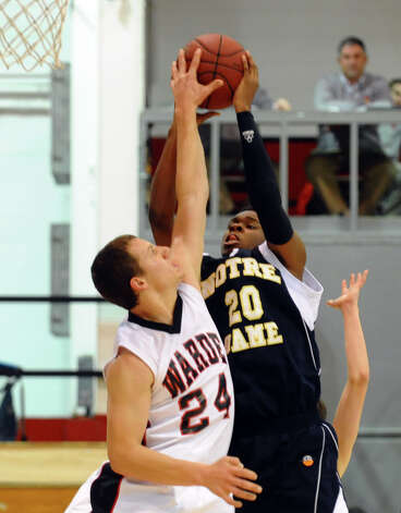 Fairfield Warde's Max Garrett blocks a shot attempt by Notre Dame of Fairfield's #20 Jaylen Jennings, during semifinal action of the Fairfield Prep Holiday Classic basketball tournament in Alumni Hall at Fairfield University in Fairfield, Conn. on Wednesday December 26, 2012. Photo: Christian Abraham / Connecticut Post