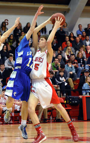 Fairfield Prep's #5 Matthew Doyle slams into Fairfield Ludlowe's #12 Ryan Foley as he tries to take the ball to the basket, during Fairfield Prep Holiday Classic basketball tournament semi final action in Alumni Hall at Fairfield University in Fairfield, Conn. on Wednesday December 26, 2012. Photo: Christian Abraham / Connecticut Post