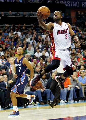Miami Heat's Dwyane Wade (3) drives past Charlotte Bobcats' Ramon Sessions (7) after being fouled during the second half of an NBA basketball game in Charlotte, N.C., Wednesday, Dec. 26, 2012. Miami won 105-92. (AP Photo/Chuck Burton) Photo: Chuck Burton