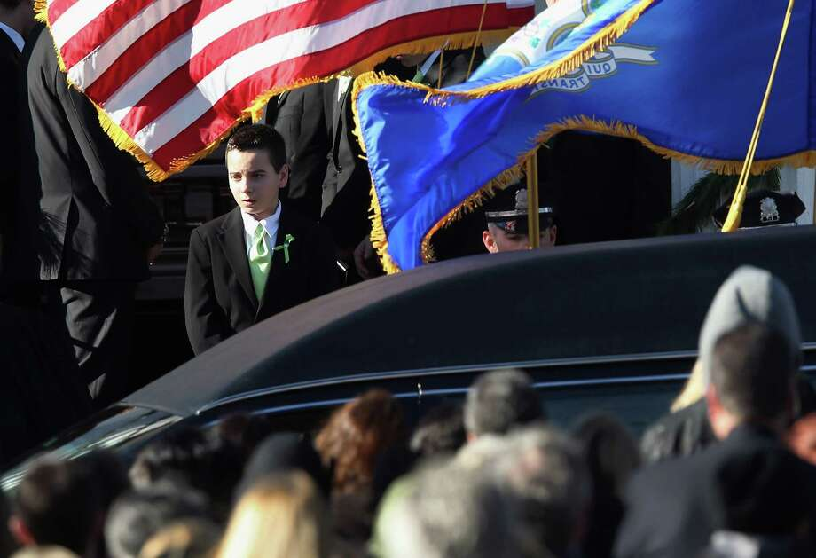 Mourners depart the funeral of slain teacher Victoria Soto, 27, at the Lordship Community Church on December 19, 2012 in Stratford, Connecticut. The first grade teacher died while reportedly trying to protect her students during last Friday's shooting massacre at Sandy Hook Elementary School in Newtown.  (Photo by John Moore/Getty Images) Photo: John Moore / Getty Images