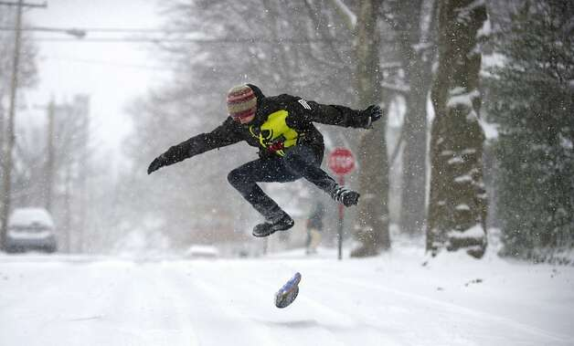 Chandler Fescemeyer, 17, snowboards down the road in Pittsburgh on Wednesday. Storms complicated other forms of travel last week. Photo: Jeff Swensen, Getty Images