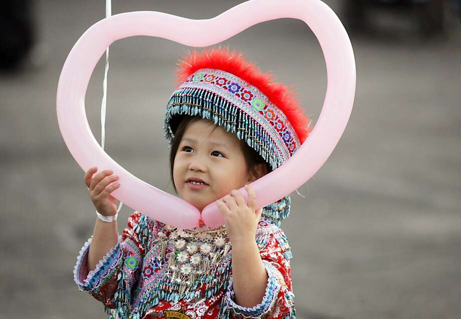 Kayla Yang, 4, of Fresno, looks through a heart-shaped balloon while wearing traditional Hmong outfit at the 2013 Hmong International New Year at the Fresno, Calif. Fairgrounds Wednesday, Dec. 26, 2012. Photo: Craig Kohlruss, Associated Press
