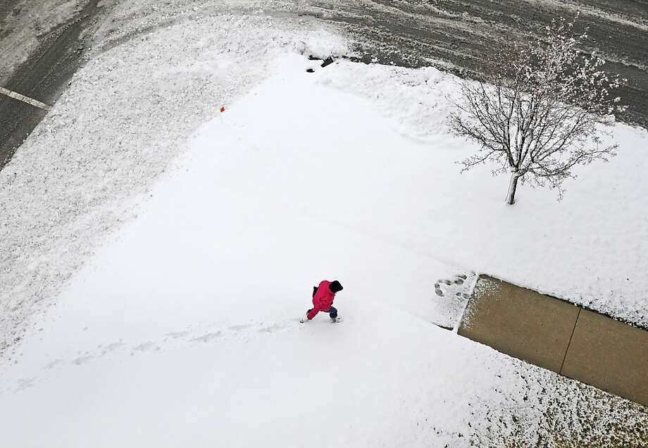 A pedestrian cuts through the snow to a cleared walkway as snow continues to fall in Carbondale, Ill. on Wednesday, Dec. 26, 2012. Photo: Aaron Eisenhauer, Associated Press