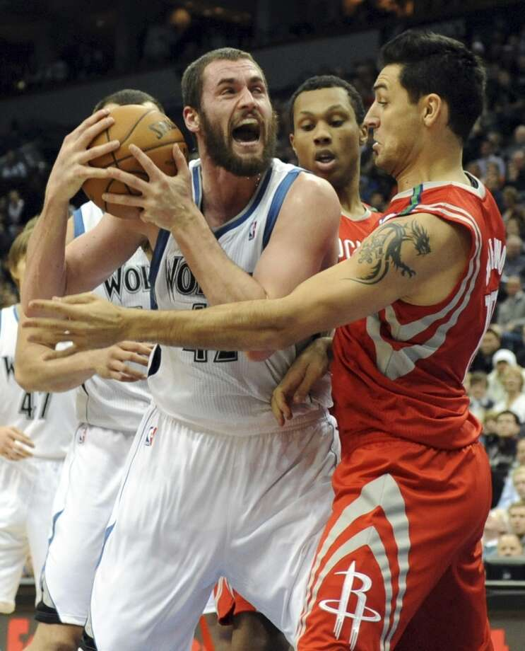 Kevin Love, left, reacts as Carlos Delfino, of Argentina, defends. (Jim Mone / Associated Press)
