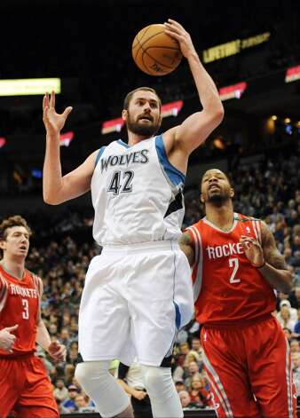 Kevin Love (42) pulls in a pass as Marcus Morris (2) and Omer Asik (3), of Turkey, watch. (Jim Mone / Associated Press)
