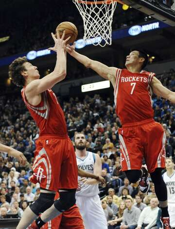 Omer Asik, left, of Turkey, and Jeremy Lin, right, reach for the rebound. (Jim Mone / Associated Press)