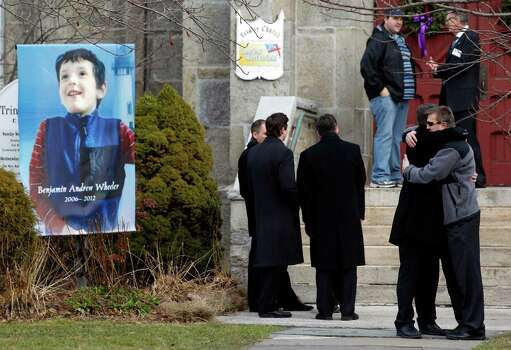Mourners embrace outside of Trinity Episcopal Church while standing next to a portrait of Benjamin Andrew Wheeler, one of the students killed in the Sandy Hook Elementary School shooting last week, Thursday, Dec. 20, 2012, in Newtown, Conn. Wheeler, 6, died when the gunman, Adam Lanza, walked into Sandy Hook Elementary School in Newtown, Dec. 14, and opened fire, killing 26 people, including 20 children, before killing himself. (AP Photo/Julio Cortez) Photo: Julio Cortez / Associated Press