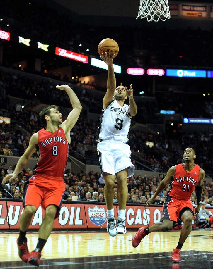 Tony Parker of the Spurs (9) scores on a fast break as Jose Calderon (8) and Terrence Ross of the Toronto Raptors defend during first-half action at the AT&T Center on Wednesday, Dec. 26, 2012. Photo: Billy Calzada, San Antonio Express-News / SAN ANTONIO EXPRESS-NEWS
