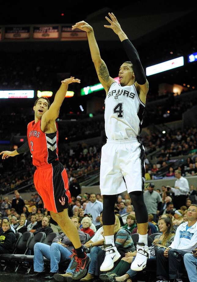 Danny Green of the Spurs scores on a three-point attempt as Landry Fields of the Toronto Raptors defends at the AT&T Center on Wednesday, Dec. 26, 2012. Photo: Billy Calzada, San Antonio Express-News / SAN ANTONIO EXPRESS-NEWS