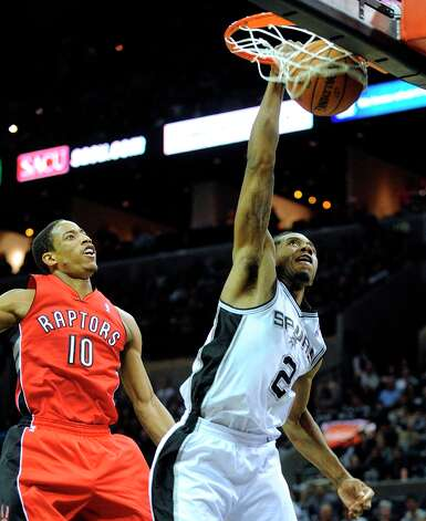 Kawhi Leonard (2) of the Spurs dunks as DeMar DeRozan of the Toronto Raptors watches during second-half action at the AT&T Center on Wednesday, Dec. 26, 2012. Photo: Billy Calzada, San Antonio Express-News / SAN ANTONIO EXPRESS-NEWS